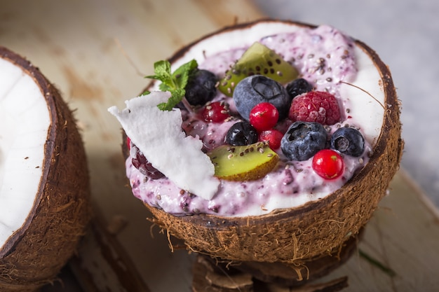 Tasty appetizing smoothie acai bowl made from blackberries and wild berries. served in coconut bowl. healthy life clean eating concept. frozen dessert nice cream.