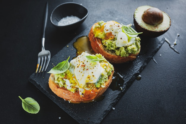 Tasty appetizing toast with avocado and egg served on dark board.