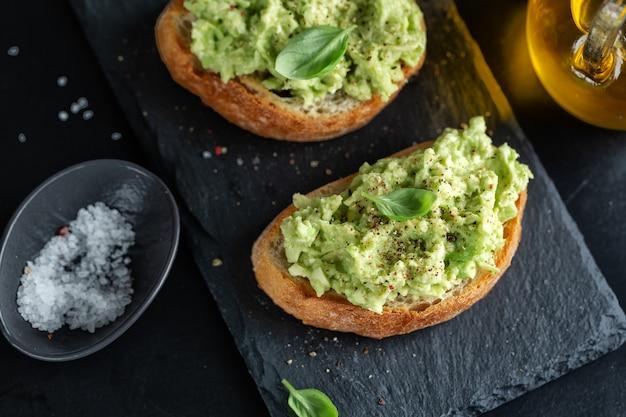 Вкусные аппетитные тосты с пюре из авокадо подаются на темной доске.