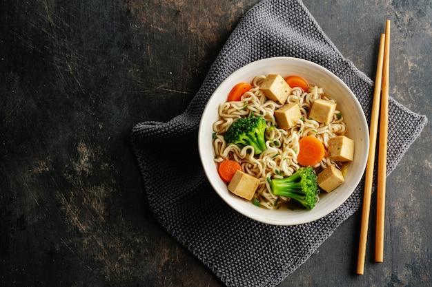 Вкусный аппетитный веганский азиатский суп с тофу, лапшой и овощами подается в миске на бетонной поверхности