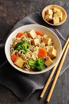 Вкусный аппетитный веганский азиатский суп с тофу, лапшой и овощами подается в миску на бетонном столе. крупный план.