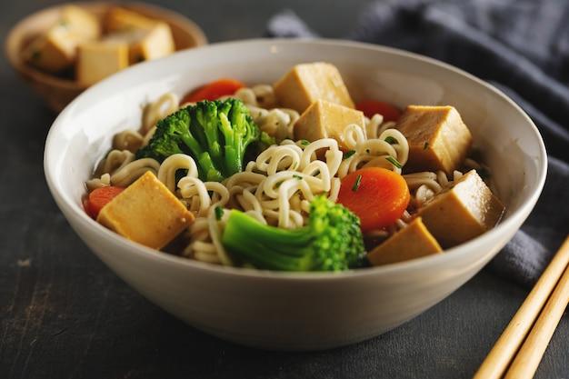 Вкусный аппетитный веганский азиатский суп с тофу, лапшой и овощами подается в миске на поверхности