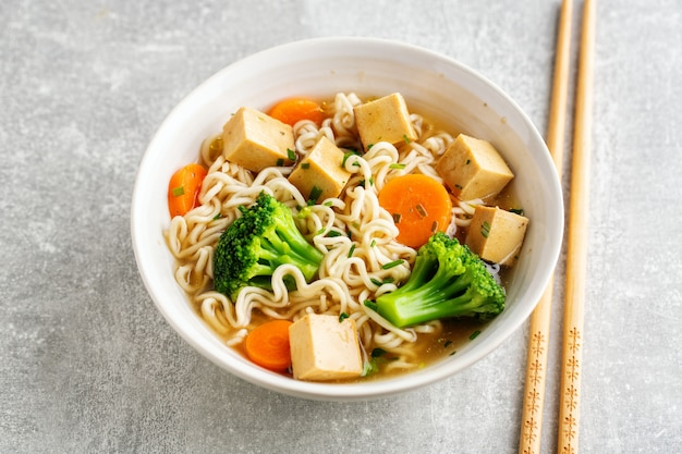 Tasty appetizing vegan asian soup with tofu, noodles and vegetables served in bowl on concrete table. closeup.