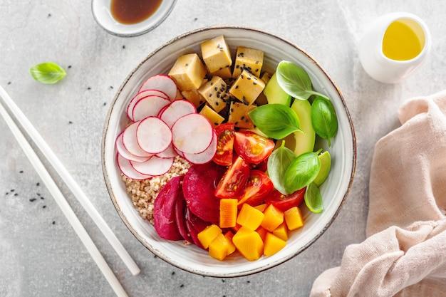 Аппетитная веганская миска с овощами и тофу подается в миске. крупный план.
