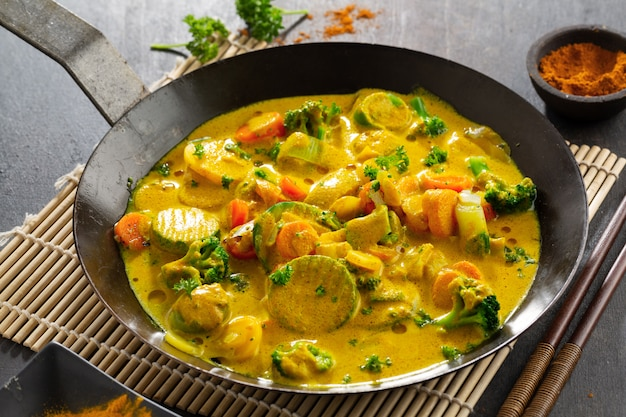 Tasty appetizing vegan curry with vegetables on pan. closeup.