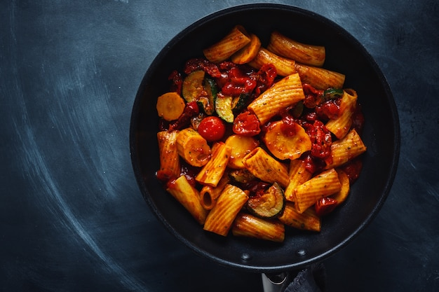Tasty appetizing vegetarian pasta with vegetables and tomato sauce served on pan. top view.