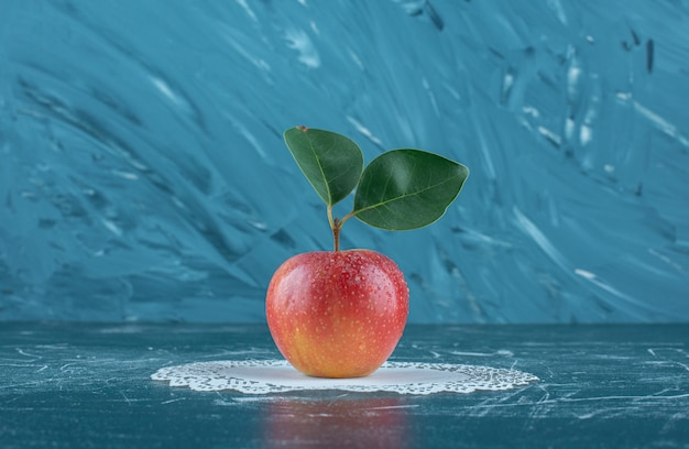Вкусное яблоко на салфетке, на синем фоне. фото высокого качества