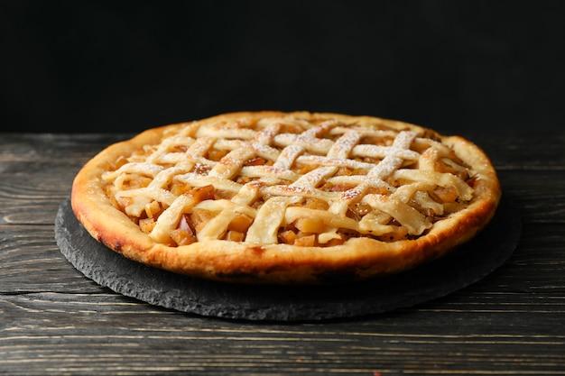 Tasty apple pie on wooden background