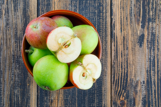 Вкусные яблоки в миске на деревянном фоне. плоская планировка.