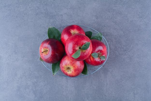 Вкусные яблоки на стеклянной тарелке на мраморном столе.