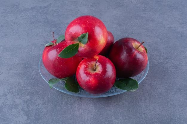 Вкусные яблоки на стеклянной тарелке на темной поверхности