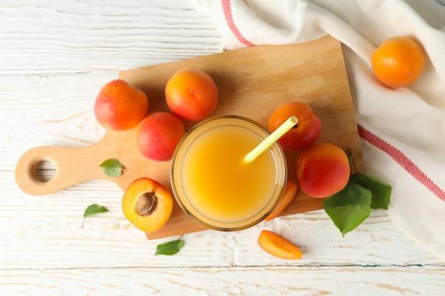 Вкусные абрикосы и сок на деревянном фоне, вид сверху