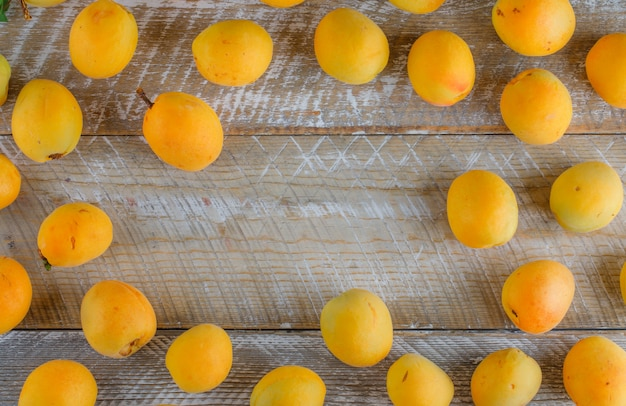 Tasty apricots on wooden table, flat lay.