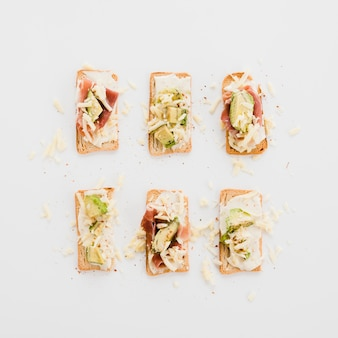 Tasty arranged toasts with cheese; avocado and bacon on white background