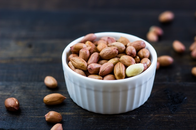A tasty arrangement of peanuts nuts in a bowl on a wooden table.