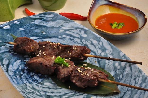 ソースとバナナの葉の上のおいしいアジアの牛肉の串焼き