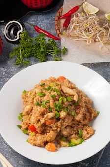Вкусный азиатский жареный чесночный рис с курицей на белой тарелке