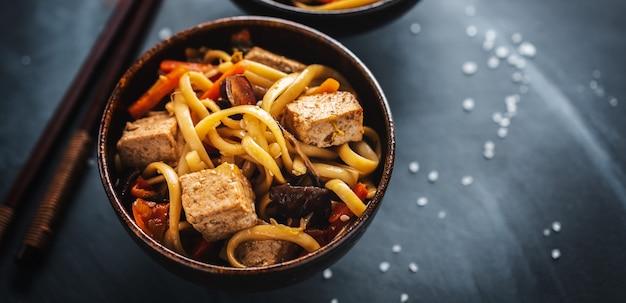 Вкусная азиатская лапша с сыром тофу и овощами в мисках. баннер.