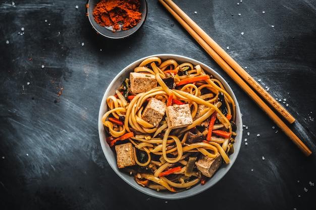 Вкусная азиатская лапша с сыром тофу и овощами на тарелках.