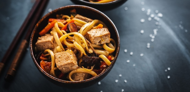 Tasty asian noodles with cheese tofu and vegetables in bowls. banner.