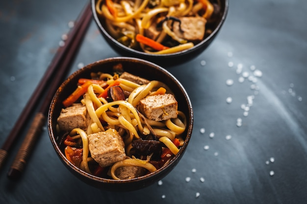 Tasty asian noodles with cheese tofu and vegetables in bowls