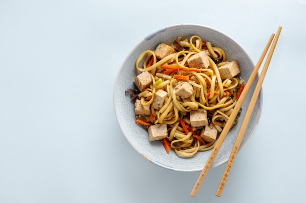 Tasty asian noodles with cheese tofu and vegetables on plates. horizontal.