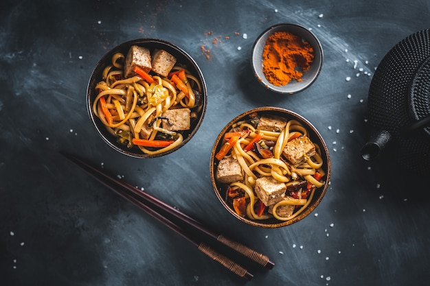 Tasty asian noodles with cheese tofu and vegetables on plates.