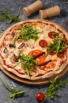 サラミ、トマト、マッシュルーム、ベーコン、サンドライトマトなど、さまざまな具材が入ったおいしいピザの盛り合わせ。垂直フレーム