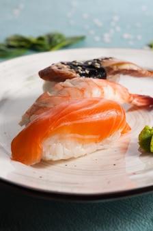 Вкусное ассорти суши на тарелке: лосось, креветки и угорь. вертикальная рамка