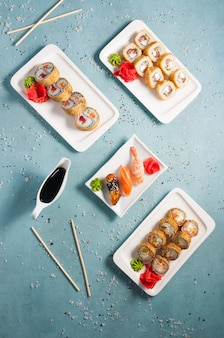 Tasty assorted sushi and rolls with soy sauce. top view