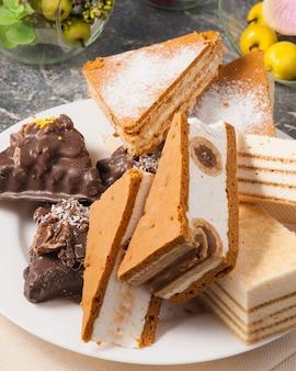プレート上のおいしい各種スイーツ:スフレケーキとブラウニーにチョコレートとナッツを添えて