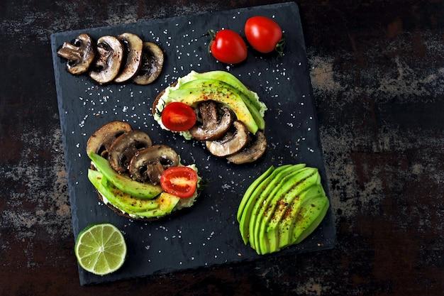 Вкусные тосты из авокадо с грибами и помидорами черри, подаются на каменной доске.