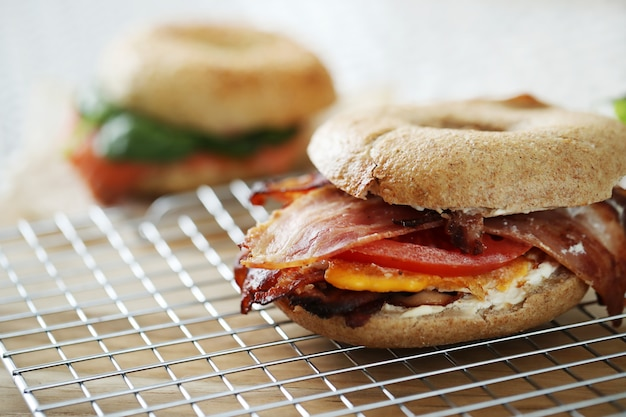 Tasty bagel sandwich with bacon