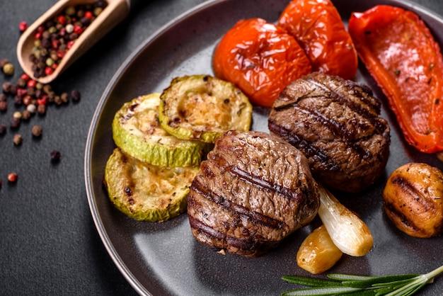 야채, 버섯, 향신료와 함께 맛있는 구운 쇠고기 메달. 구운 요리