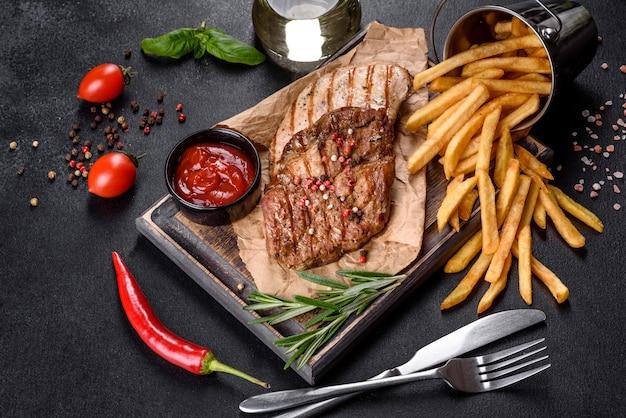 야채, 감자 튀김, 향신료와 함께 맛있는 구운 쇠고기 스테이크. 구운 요리