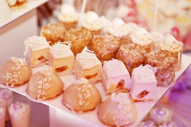 Вкусные запеченные пирожные с белыми кремами, подаются на белой тарелке