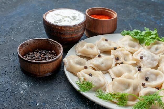 Gustosi gnocchi al forno all'interno del piatto insieme a yogurt e verdure sulla scrivania grigio scuro