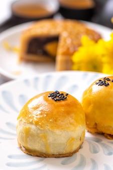 밝은 시멘트 테이블 배경에서 중추절을 위한 맛있는 구운 달걀 노른자 페이스트리 월병. 중국 전통 음식 개념을 닫고 공간을 복사합니다.
