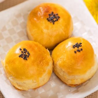 明るい木製のテーブルの背景に中秋節のおいしい焼き卵黄ペストリー月餅。中国のお祭り料理のコンセプト、クローズアップ、コピースペース。