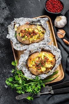 Tasty baked potato topped with cheddar cheese, garlic and parsley. top view