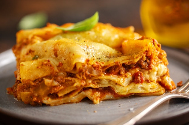Tasty baked prepared classic italian lasagne in casserole on bright background. closeup