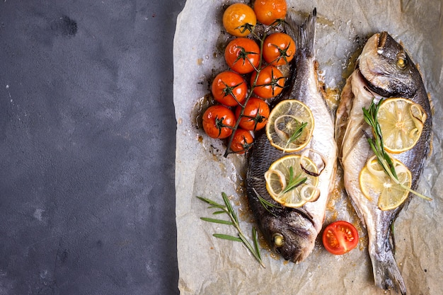 Tasty baked whole fish on baking paper. baked sea bream with lemon, onion, herbs, cherry tomatoes, spices on dark rustic background. grilled delicious fish.