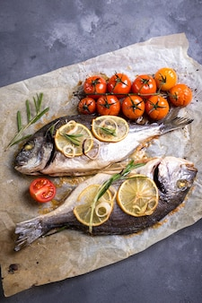 Tasty baked whole fish on baking paper. baked sea bream with lemon, onion, herbs, cherry tomatoes, spices on dark rustic background.