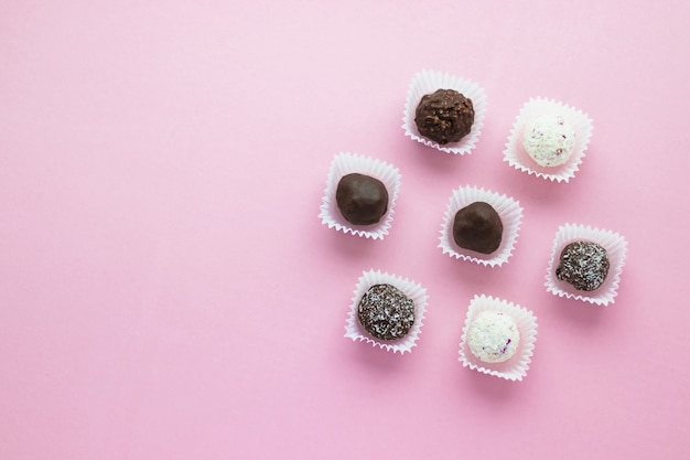 Вкусные шоколадные конфеты в форме шаров, упакованные в небольшие бумажные корзинки на розовом фоне. романтический десерт дня святого валентина. вкусное сладкое. минималистичный стиль. плоская планировка, вид сверху с копией scape.