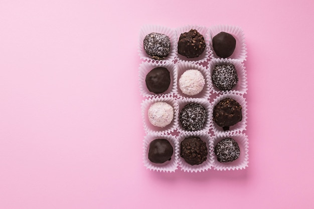 Tasty ball-shaped chocolate candies packed in small paper baskets on pink background. romantic valentine's day day dessert. delicious sweet. minimal style. flat lay, top view with copy scape.