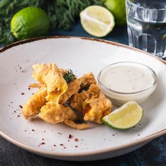 Вкусная рыба в кляре на тарелке с белым соусом и лаймом