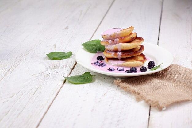 ミントの葉が付いている軽い木のテーブルの上のブルーベリーおよびブルーベリーヨーグルトが付いているおいしい美しいパンケーキ。