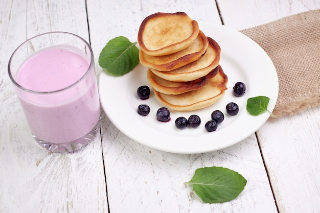 Вкусные красивые блины с черникой и черничным йогуртом на светлом деревянном столе с листьями мяты.
