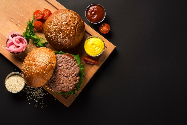 Tasty beef burgers on a wooden board with sauces