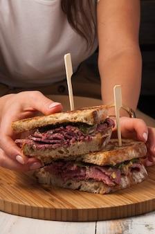 女の子の手においしいビーフサンドイッチ。